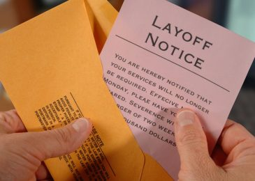 AM4FCE A man removes a lay-off notice from an envelope